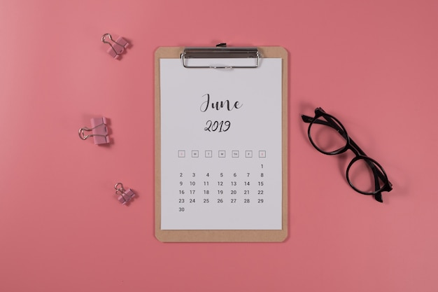 Flat lay calendar with clipboard and glasses on pink background. june 2019. top view.