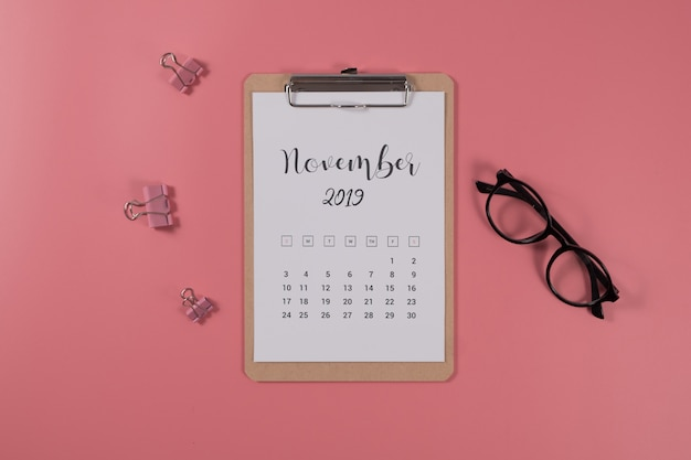 Flat lay calendar with clipboard and glasses on pink background. november 2019. top view.