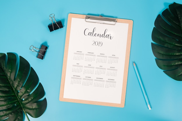 Flat lay calendar with clipboard, palm leaves and pencil on blue background.