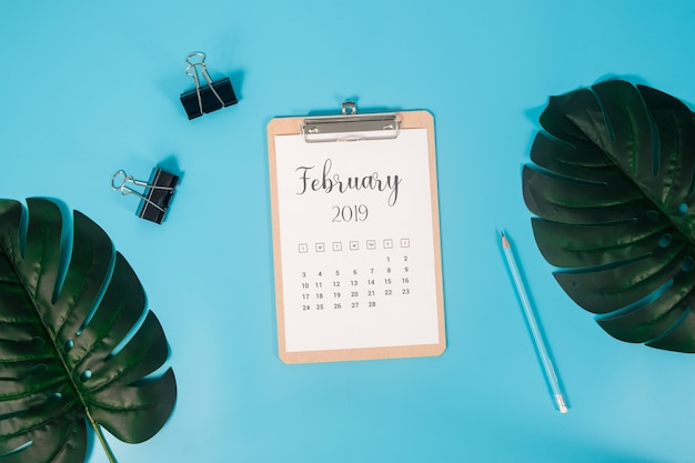 Flat lay calendar with clipboard, palm leaves and pencil on blue background