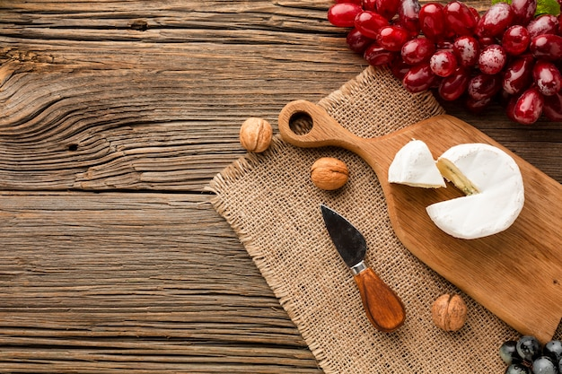 Flat lay camembert grapes and walnuts on wooden cutting board with copy space