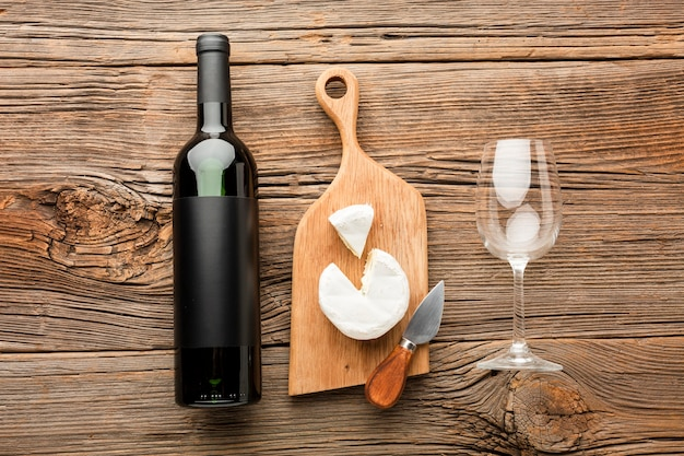Flat lay camembert on wooden cutting board wine and glass