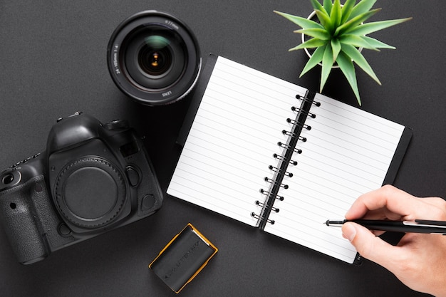 Flat lay of camera lenses and notebook on black background