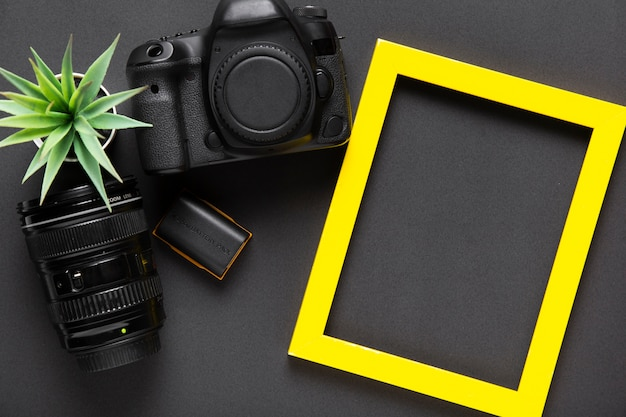 Flat lay of camera and yellow frame