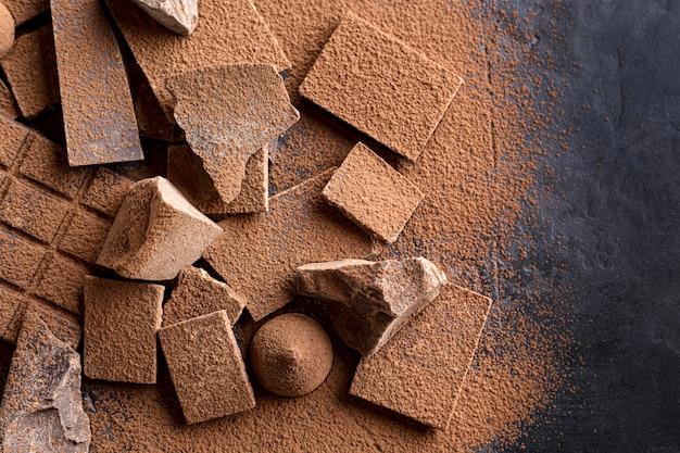 Piatto disteso di caramelle con cioccolato e cacao in polvere