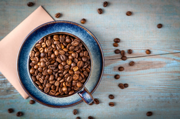 Flat lay cappuccino cup with coffee beans scattered on table, blue coffee cup top view closeup on wooden background in sun light