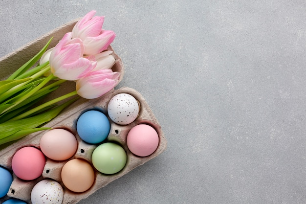 Flat lay of carton with colorful easter eggs and tulips
