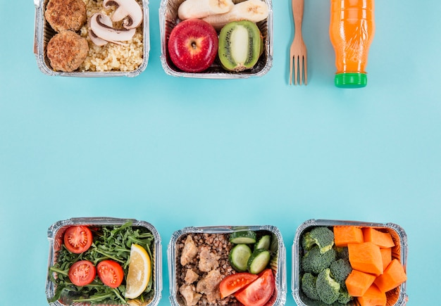 Flat lay of casseroles with fruits and meals