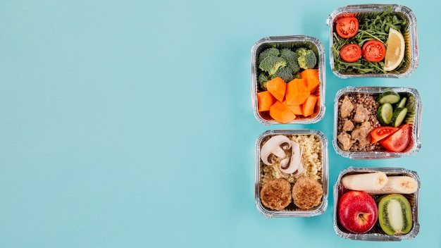 Flat lay of casseroles with meals and copy space