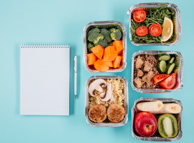 Flat lay of casseroles with meals and notebook