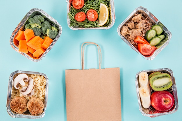Flat lay of casseroles with meals and paper bag