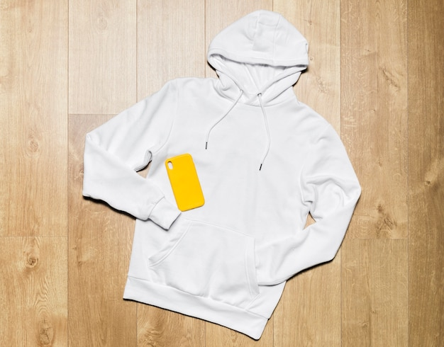 Flat lay casual white hoodie with phone case