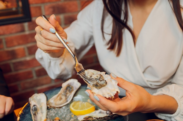 Flat lay of caucasian hands holding oysters with other seafood dishes on a dark table.