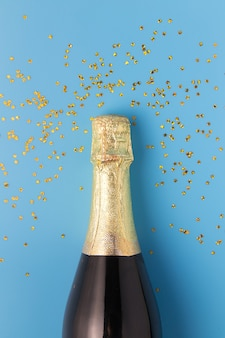 Flat lay of celebration, champagne bottle on blue background with glitter.