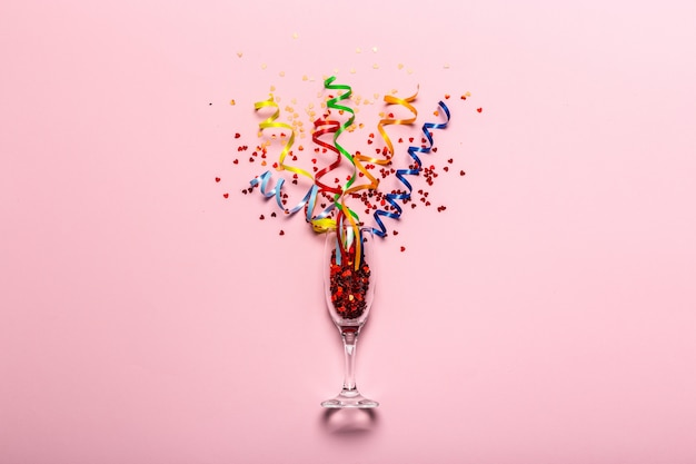 Flat lay of celebration. champagne glass with colorful party streamers