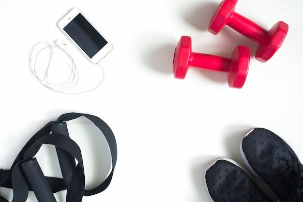 Flat lay di cellulare, dumbbells rossi e attrezzature sportive su sfondo bianco. abbigliamento sportivo, sport fashion, accessori sportivi, attrezzatura sportiva, vista dall'alto