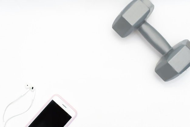 Flat lay of cellphone, red dumbbells and sport equipment on white background.