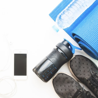 Flat lay of cellphone with blue color yoga mat, bottle of water and black sneakers on white background, working out and healthy concept, top view
