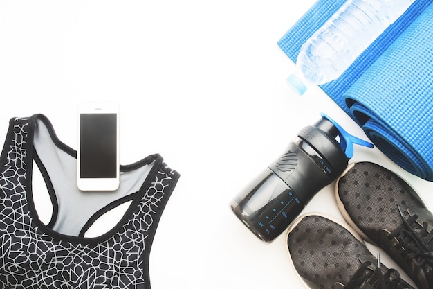 Flat lay of cellphone with sport bra, blue color yoga mat, bottle of water and black sneakers on white background, working out and healthy concept, top view