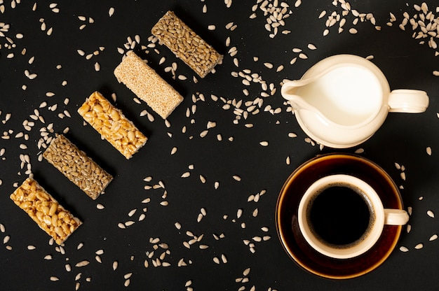 Flat lay cereal bars assortment with milk and coffee on plain background