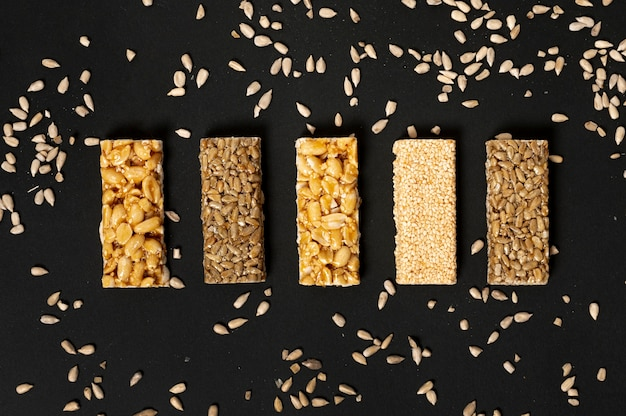 Flat lay cereal bars assortment with sunflower seeds on plain background