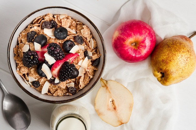 Flat lay cereal and forest fruits in bowl with milk