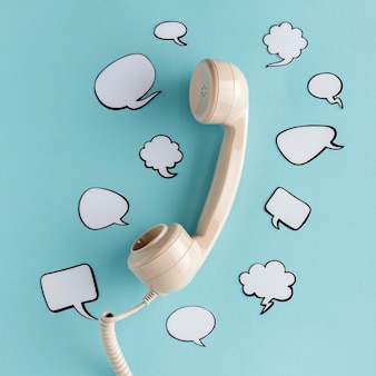 Flat lay of chat bubbles with telephone receiver