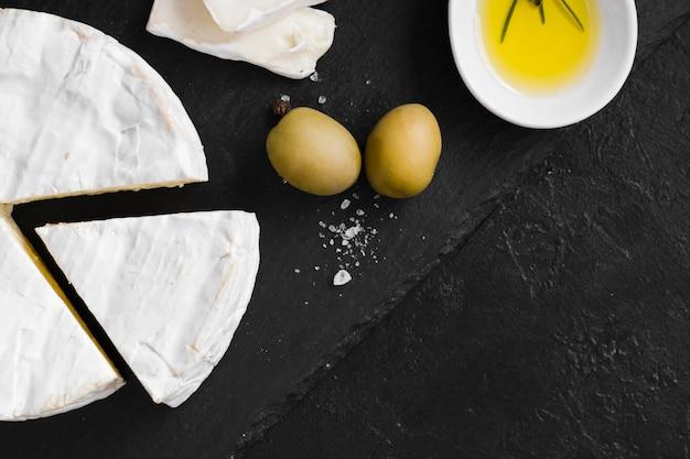Плоская композиция для сыра на черном фоне