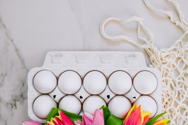 Flat lay chicken eggs and colorful tulips, eco bag on marble background