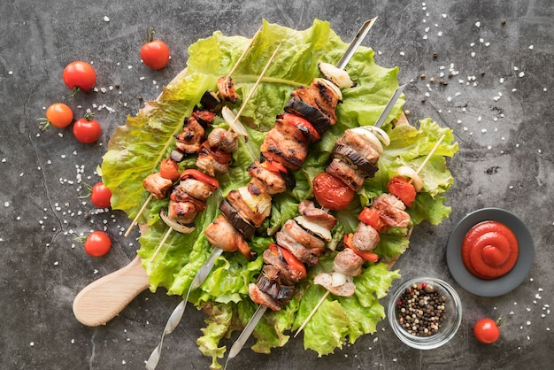 Flat lay chicken grilled skewers with vegetables