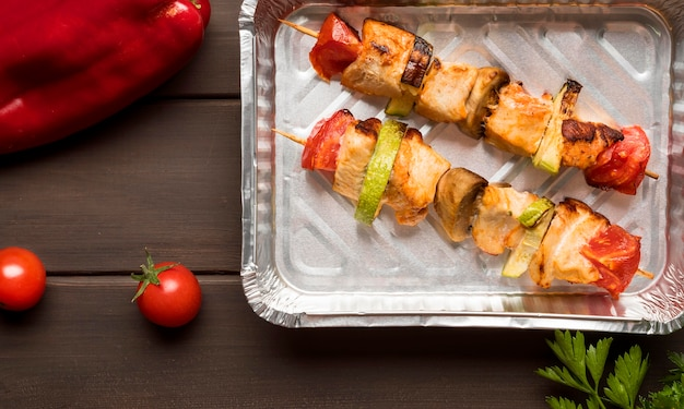 Flat lay chicken skewers on tray with red pepper and tomatoes