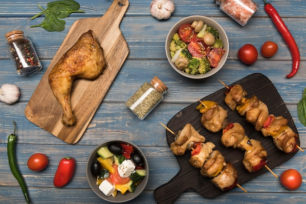 Flat lay chicken and skewers on wooden board and ingredients with ingredients