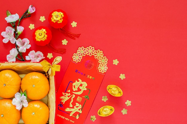 Flat lay of chinese new year festival decoration on red background. chinese language on ingot means blessing, on money red packet means œgood omens.