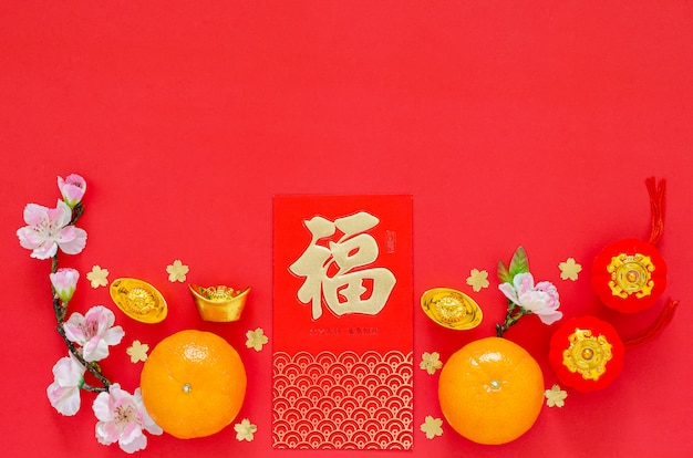 Flat lay of chinese new year festival decoration on red background. chinese language on ingot and money red packet means blessing