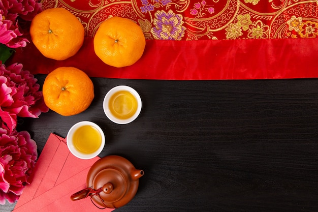 플랫 누워 중국 새 해 만다린 오렌지와 블랙 컬러 나무 bakcground에 평면도와 차 물.