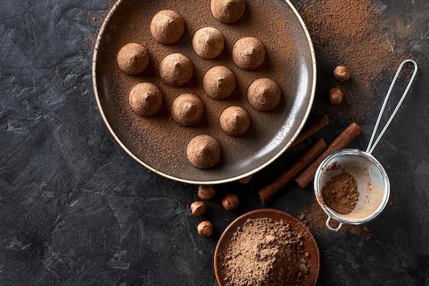 Piatto disteso di caramelle al cioccolato con cacao in polvere e bastoncini di cannella