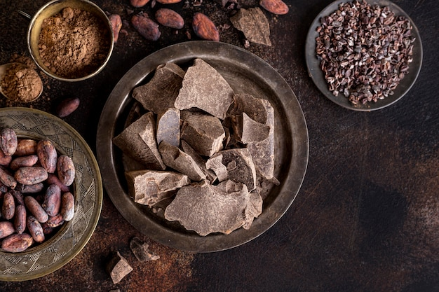 Flat lay of chocolate chunks on plate with cocoa beans and powder