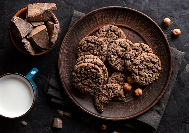 Flat lay of chocolate cookies on plate with hazelnuts and milk