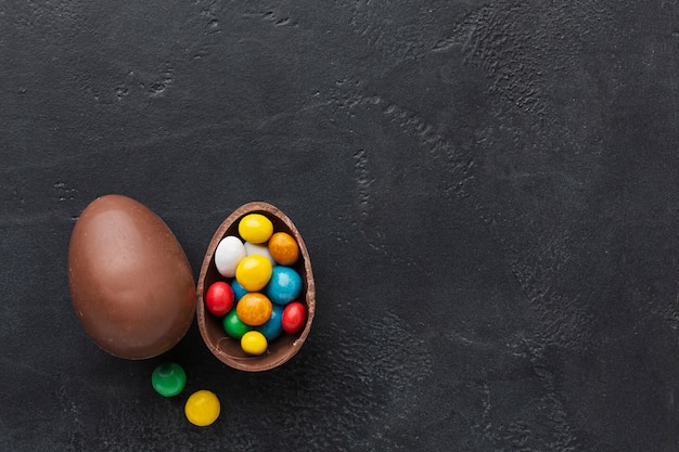 Flat lay of chocolate easter egg with colorful candy and copy space