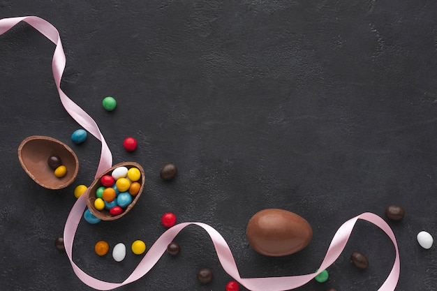 Flat lay of chocolate easter eggs filled with colorful candy and copy space