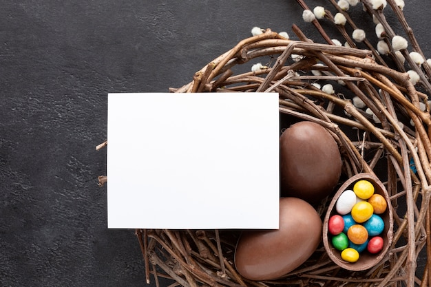 Flat lay of chocolate easter eggs filled with colorful candy in nest
