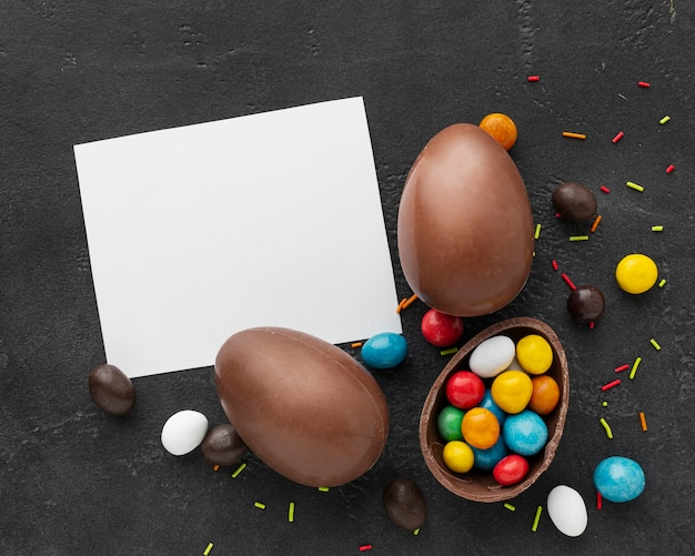 Flat lay of chocolate easter eggs with colorful candy and piece of paper