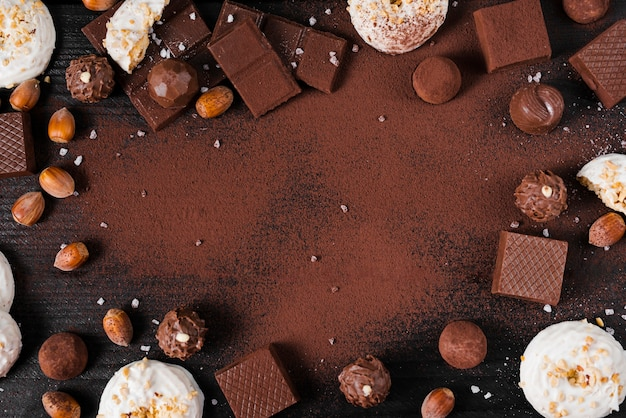 Flat lay chocolate sweets mix and cocoa powder on pink background with copy space