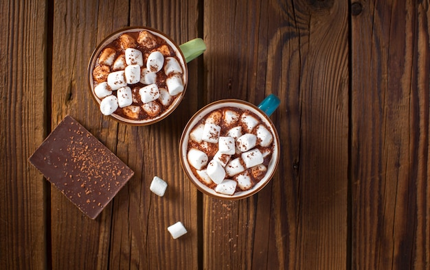 Flat lay chocolate tablet and hot chocolates with marshmallows