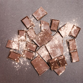 Flat lay chocolate tablets covered in cocoa powder
