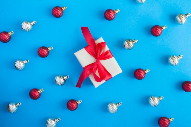 Flat lay of christmas balls and gift box on the blue background. top view. close-up.