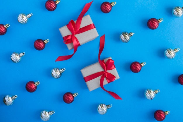Flat lay of christmas balls and gift box on the blue background. top view.