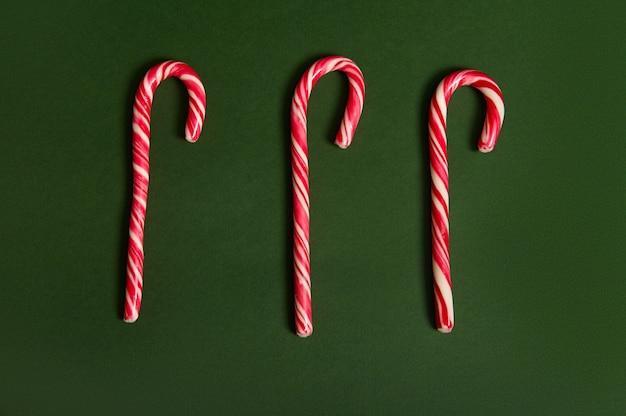 コピースペースのある濃い緑色の背景に、白と赤の砂糖のような甘いロリポップキャンディケイン3本のフラットレイクリスマスコンポジション。 2つの対照的な色の食品組成