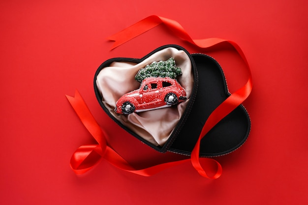 Flat lay christmas composition. small red toy car in a black box in the form of a heart with a red ribbon on red.