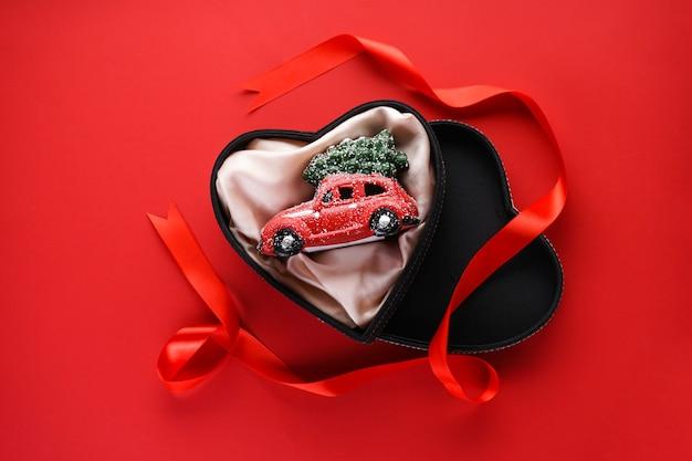 Плоская планировка рождественская композиция. маленькая красная игрушечная машинка в черной коробке в форме сердца с красной лентой на красном.